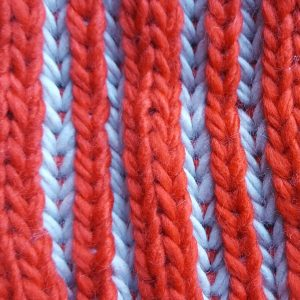 detalle tejido del gorro de punto rayas rojas y grises con pompon