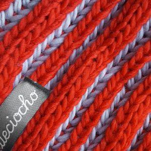 detalle del gorro de punto rayas rojas y grises con pompon
